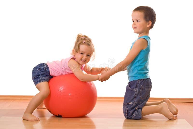Rapaz pequeno que ensina lhe a ginástica da irmã imagem de stock royalty free