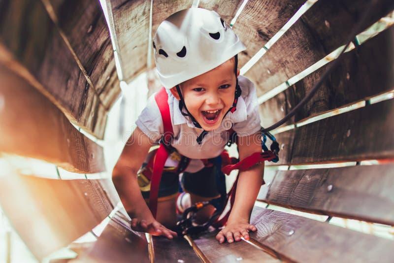Rapaz pequeno que escala no parque da atividade da aventura com capacete fotos de stock
