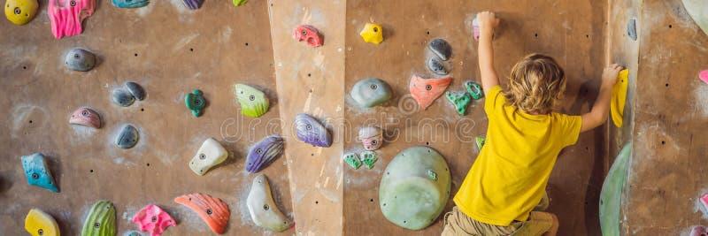 Rapaz pequeno que escala uma parede da rocha em botas especiais BANDEIRA interna, FORMATO LONGO imagens de stock
