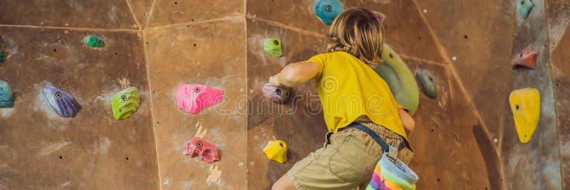 Rapaz pequeno que escala uma parede da rocha em botas especiais BANDEIRA interna, FORMATO LONGO fotografia de stock royalty free