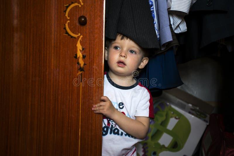Rapaz pequeno que esconde dentro do vestuário imagens de stock