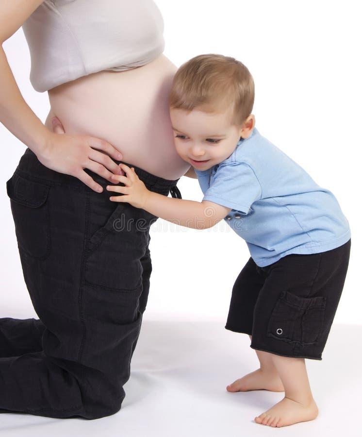 Rapaz pequeno que escuta a barriga grávida da mamã imagem de stock royalty free