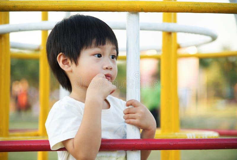 Rapaz pequeno que espera e que procura seu pai no playgroun foto de stock