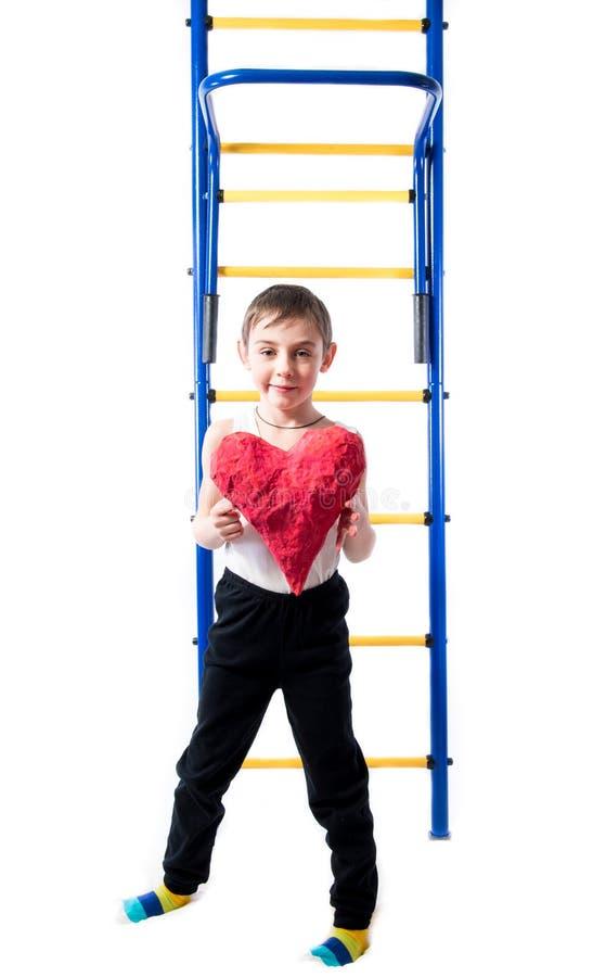 Rapaz pequeno que está ao lado das escadas coloridas e que guarda um coração vermelho imagem de stock royalty free