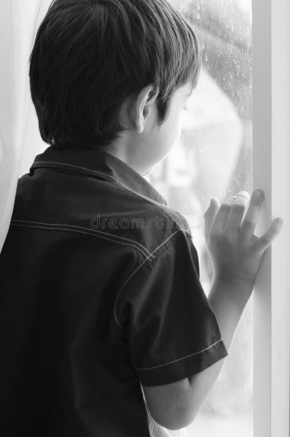Rapaz pequeno que está atrás da porta preto e branco imagem de stock royalty free