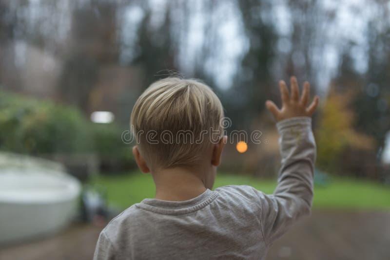 Rapaz pequeno que está olhando fixamente fora de uma janela imagens de stock