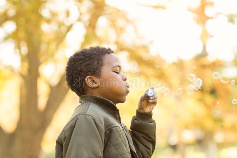 Rapaz pequeno que faz algumas bolhas imagens de stock