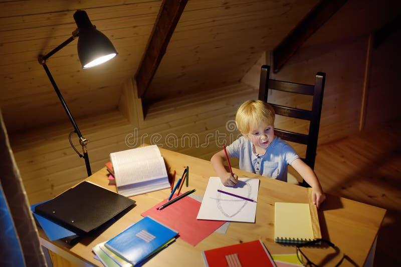 Rapaz pequeno que faz trabalhos de casa, pintando e escrevendo em casa o nivelamento A criança em idade pré-escolar aprende liçõe foto de stock