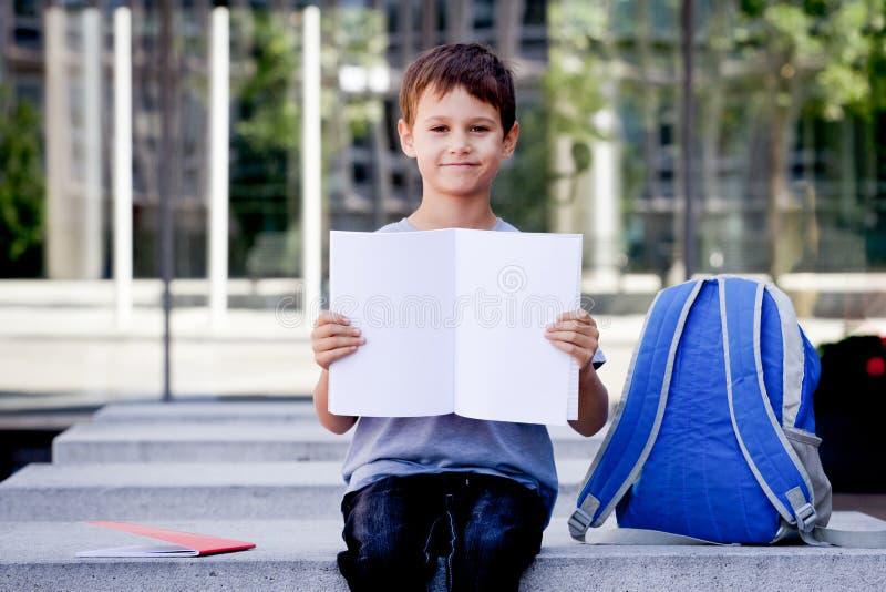 Rapaz pequeno que guarda o caderno aberto da placa com espaço da cópia para o texto fotografia de stock royalty free