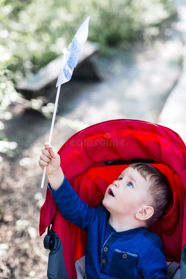 Rapaz pequeno que guarda um moinho de vento de papel ao sentar-se em seu pram fotos de stock royalty free