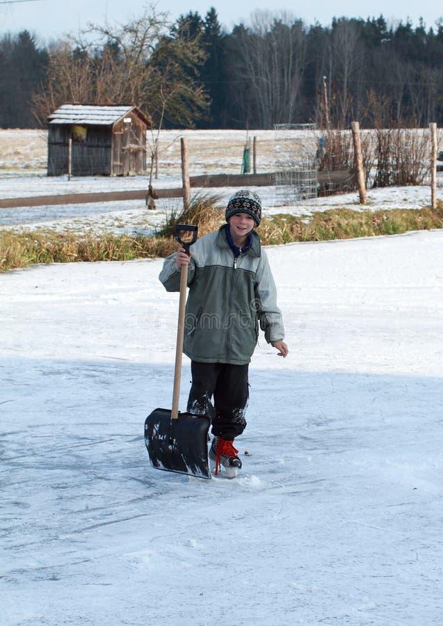 Rapaz pequeno que guardara o gelo-líquido de limpeza na lagoa imagens de stock royalty free