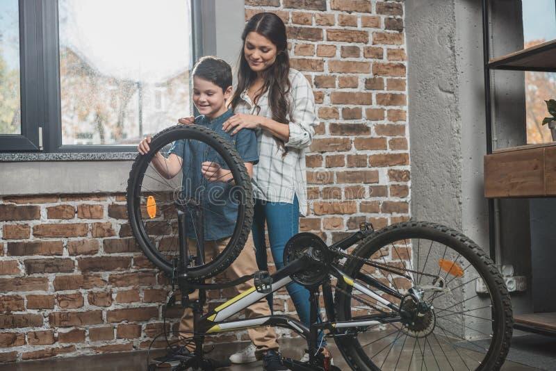 Rapaz pequeno que instala uma roda nova em sua bicicleta quando sua mãe estiver fotografia de stock royalty free