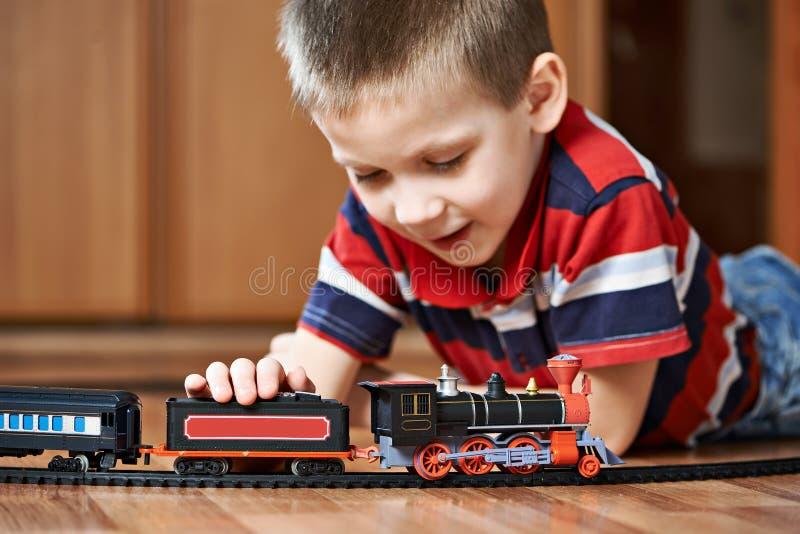 Rapaz pequeno que joga com a estrada de ferro que encontra-se no assoalho fotos de stock royalty free