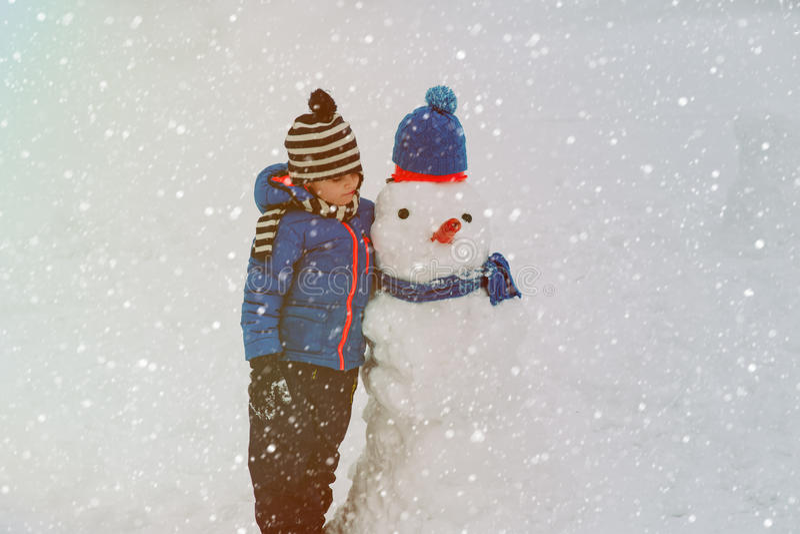 Rapaz pequeno que joga com o boneco de neve na natureza foto de stock royalty free