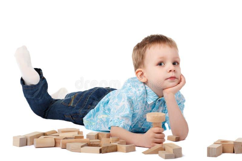 Rapaz pequeno que joga com o desenhista de madeira no assoalho fotografia de stock royalty free