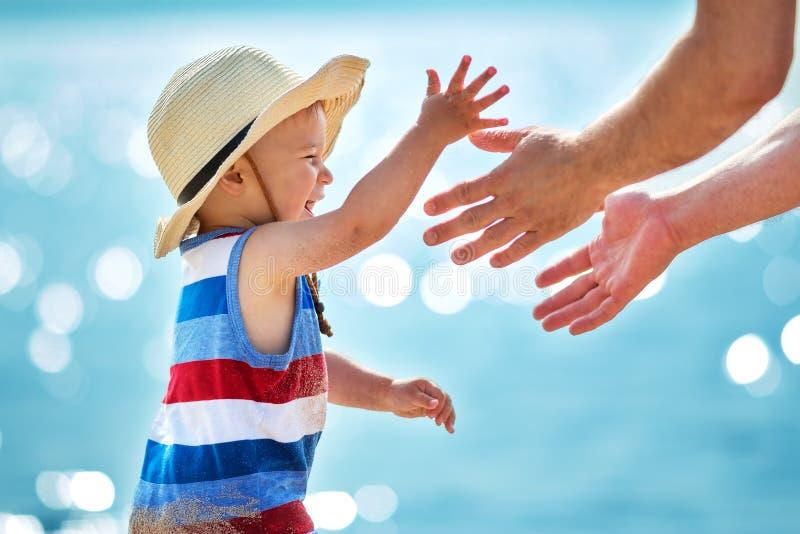 Rapaz pequeno que joga com o pai na praia no chapéu de palha foto de stock royalty free