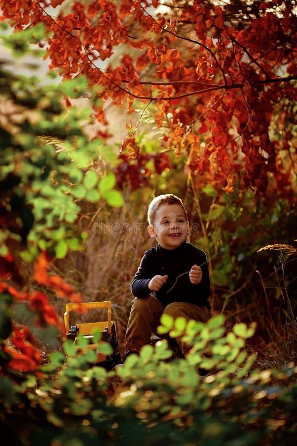 Rapaz pequeno que joga com o trator do brinquedo na estrada do campo imagens de stock royalty free