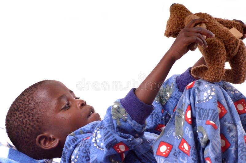 Rapaz pequeno que joga com seu urso de peluche imagens de stock royalty free