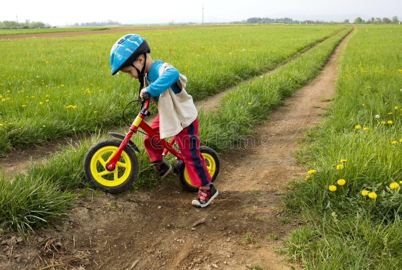 Rapaz pequeno que joga com sua bicicleta. fotografia de stock royalty free