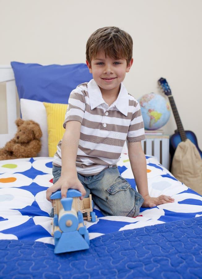 Rapaz pequeno que joga com um trem em seu quarto imagem de stock