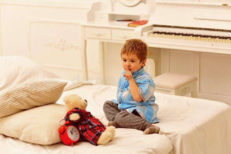 Rapaz pequeno que joga com urso dia feliz da família e das crianças Jogo do rapaz pequeno em casa Brinquedos da brincadeira Infân imagem de stock