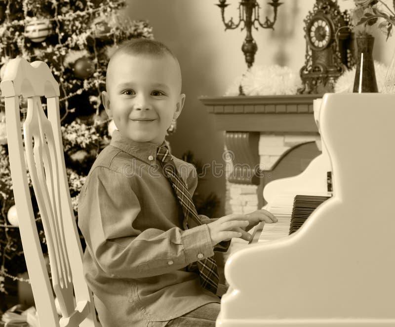 Rapaz pequeno que joga em um piano de cauda branco fotos de stock