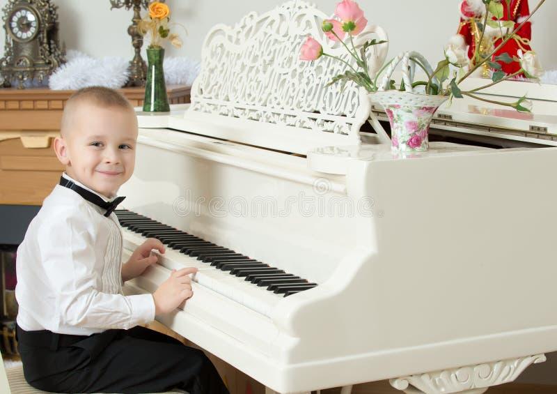 Rapaz pequeno que joga em um piano de cauda branco imagens de stock