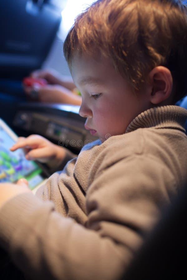 Rapaz pequeno que joga em um tablet pc foto de stock royalty free