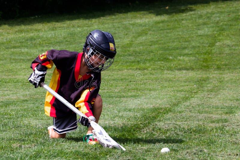 Rapaz pequeno que joga na lacrosse protetora da engrenagem no parque imagens de stock royalty free