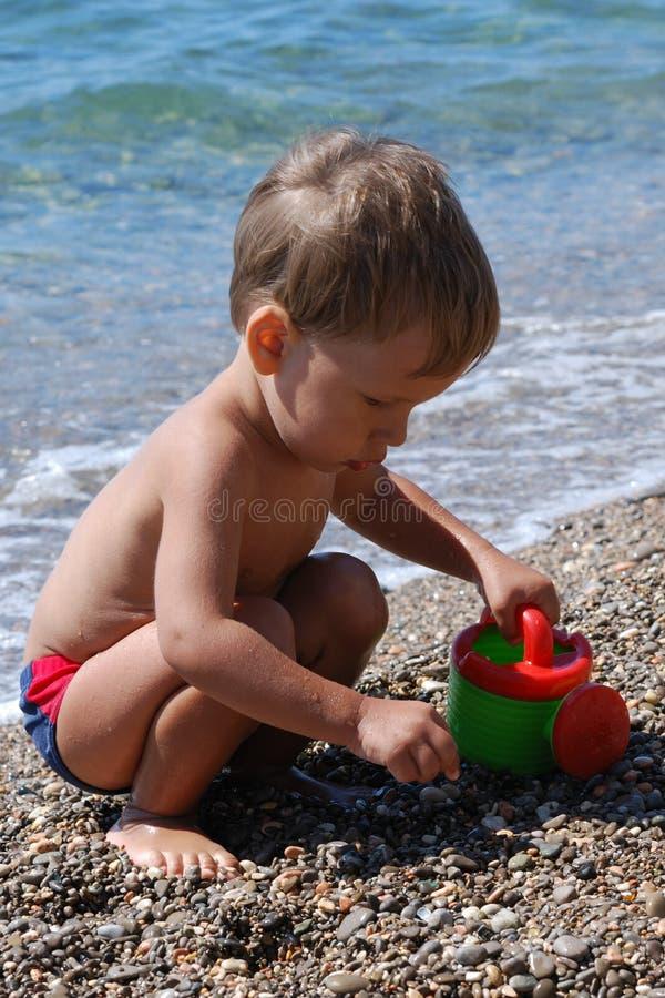 Rapaz pequeno que joga na praia imagens de stock royalty free