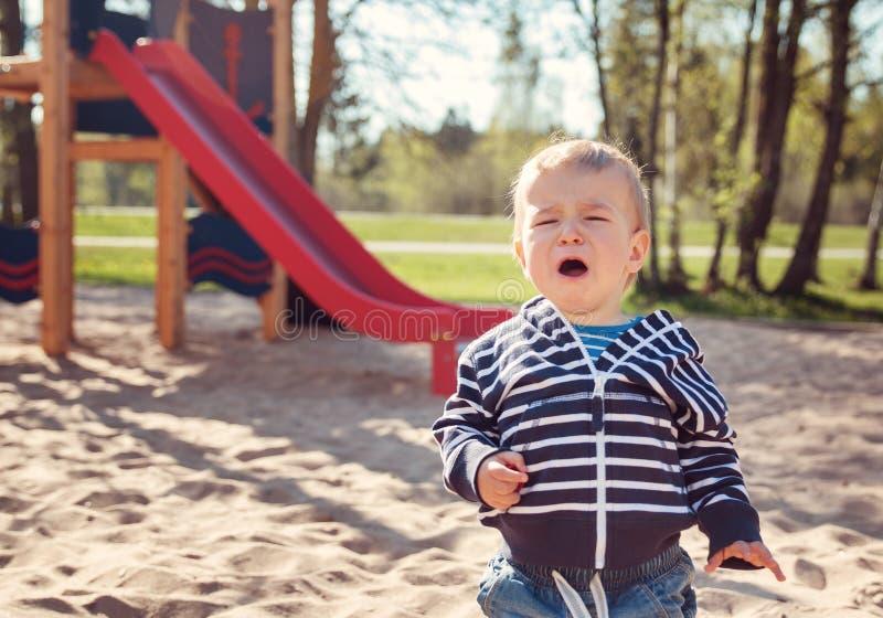 Rapaz pequeno que joga no campo de jogos e no grito fotos de stock