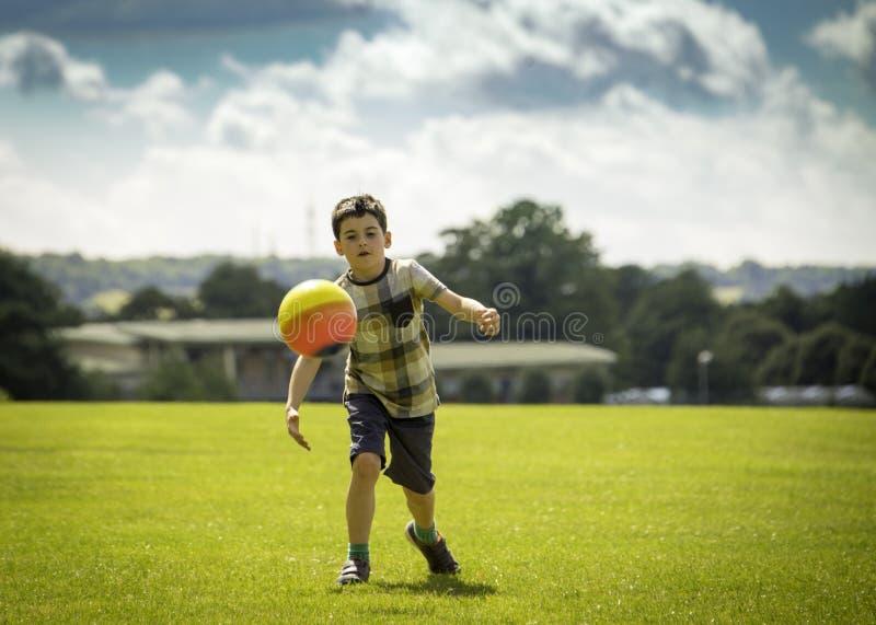 Rapaz pequeno que joga o futebol no parque fotografia de stock