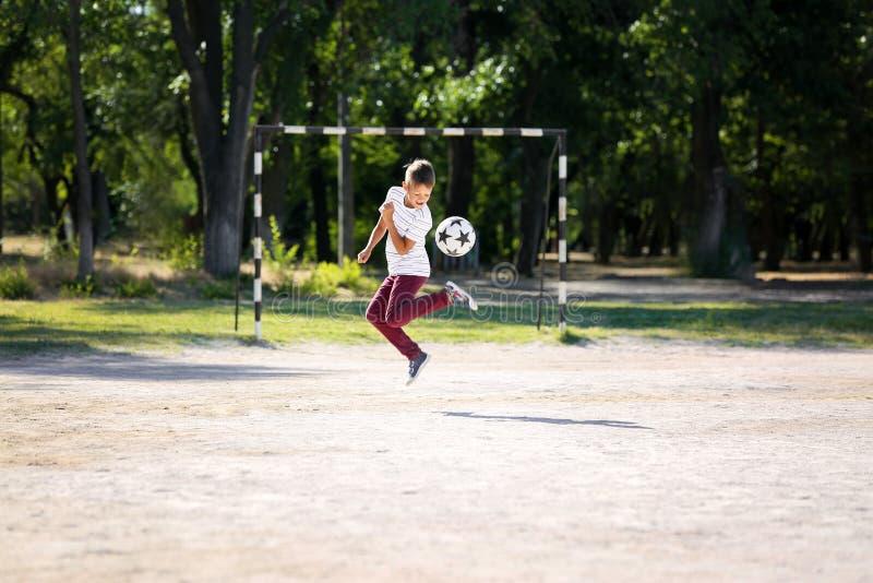 Rapaz pequeno que joga o futebol no passo do futebol imagens de stock royalty free