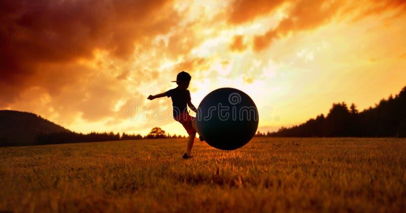 Rapaz pequeno que joga o futebol no prado fotos de stock