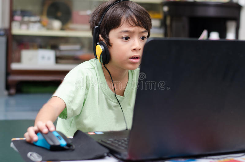 Rapaz pequeno que joga o jogo de computador em casa fotos de stock royalty free