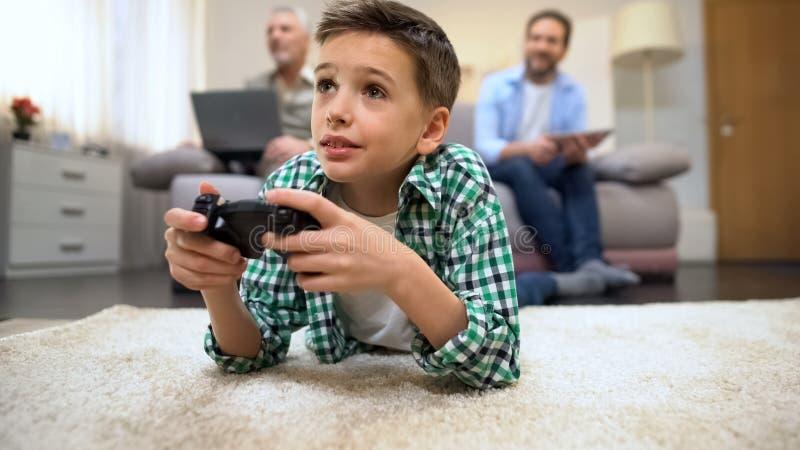 Rapaz pequeno que joga o jogo de vídeo que encontra-se no sorriso do assoalho, do pai e do avô foto de stock royalty free