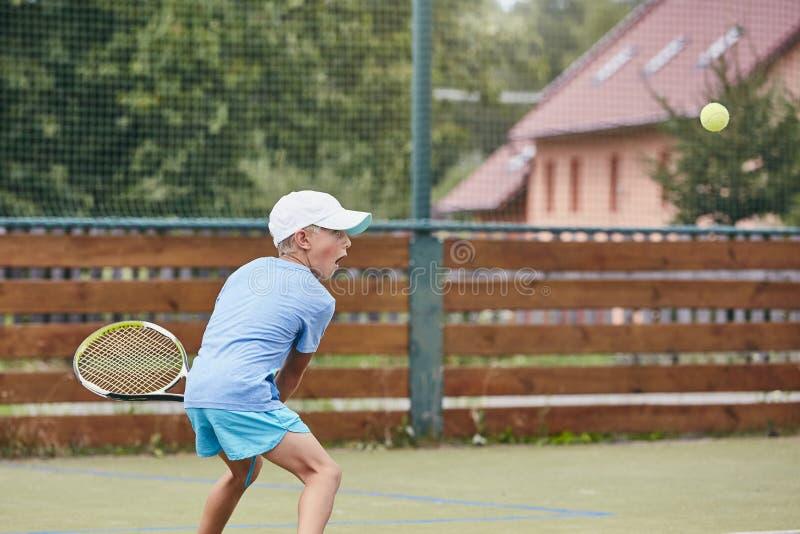 Rapaz pequeno que joga o tênis fotos de stock