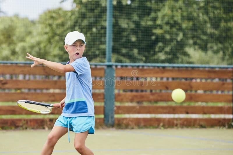 Rapaz pequeno que joga o tênis imagens de stock royalty free