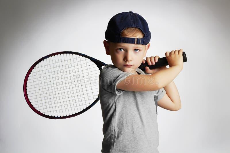 Rapaz pequeno que joga o tênis Crianças do esporte Criança com raquete de tênis imagens de stock