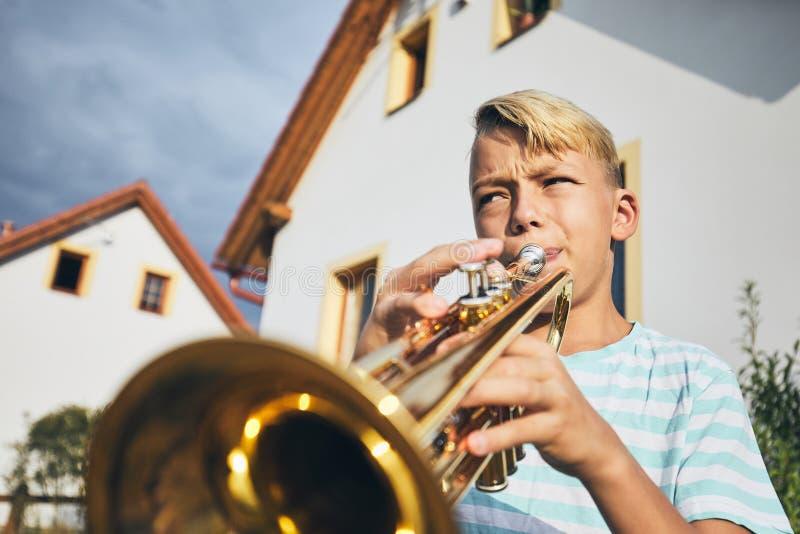 Rapaz pequeno que joga a trombeta fotografia de stock