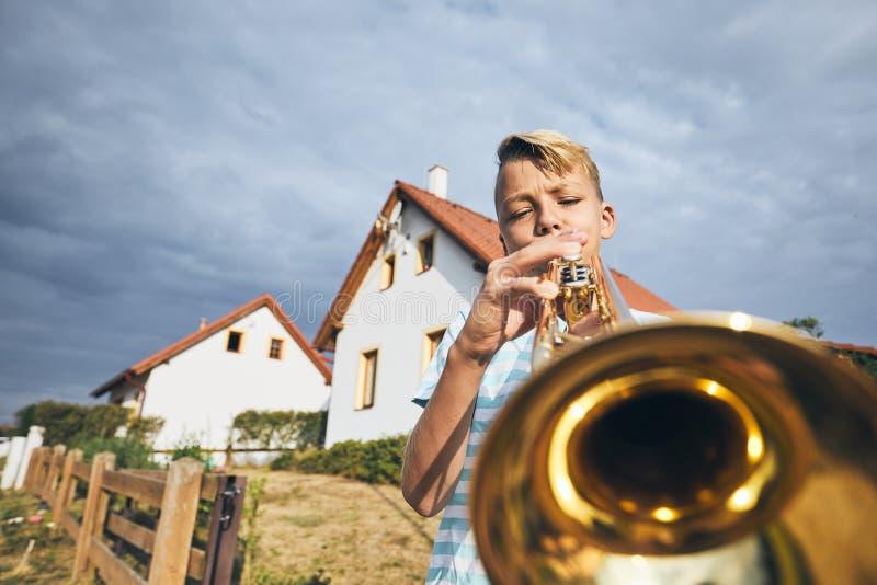 Rapaz pequeno que joga a trombeta fotos de stock