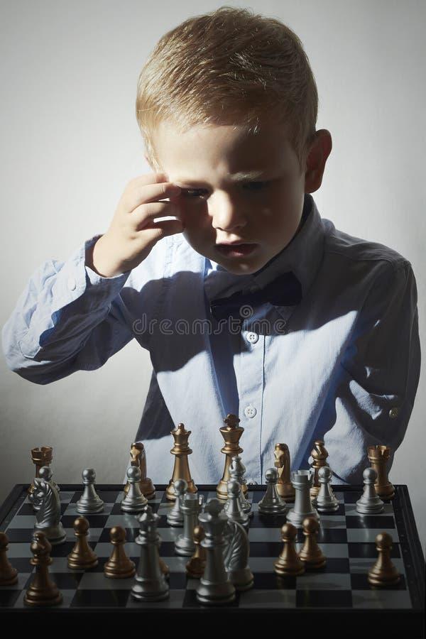 Rapaz pequeno que joga a xadrez Criança pequena esperta do gênio Jogo inteligente Tabuleiro de xadrez imagens de stock