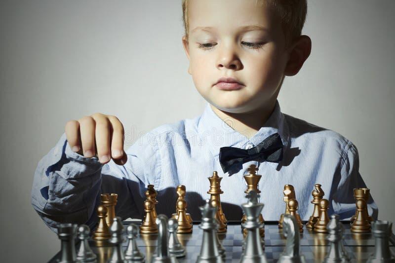 Rapaz pequeno que joga a xadrez Miúdo esperto criança do gênio Jogo inteligente Tabuleiro de xadrez imagem de stock