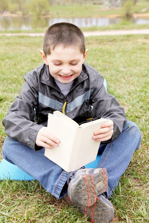 Rapaz pequeno que lê o livro engraçado imagem de stock