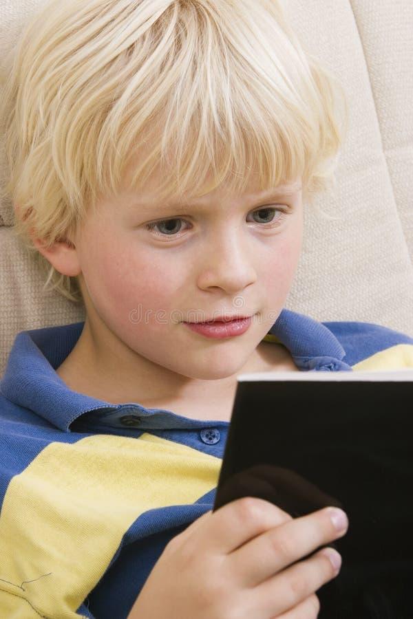 Rapaz pequeno que lê um livro fotografia de stock