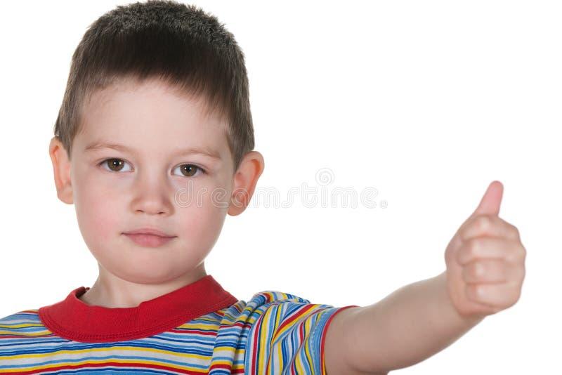 Rapaz pequeno que mantem seu polegar imagem de stock