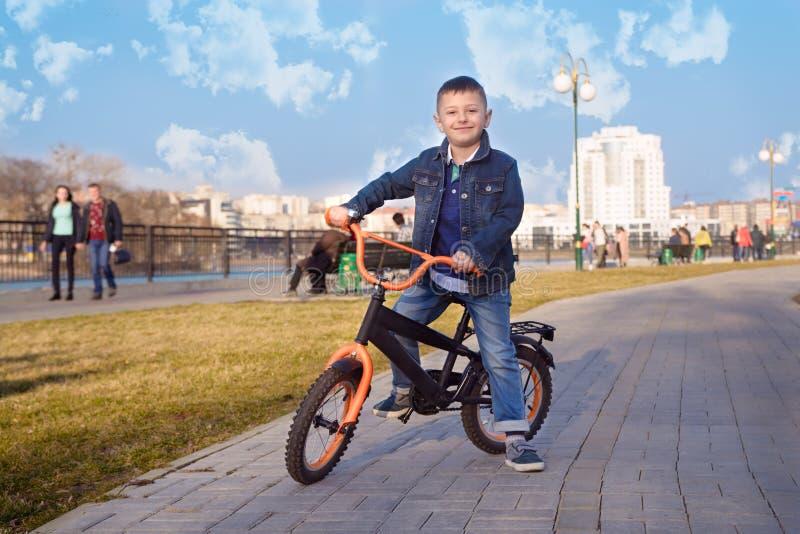 Rapaz pequeno que monta sua bicicleta no parque da cidade fotos de stock