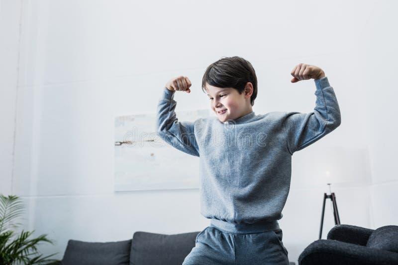 Rapaz pequeno que mostra o bíceps e que tem o divertimento em casa imagem de stock