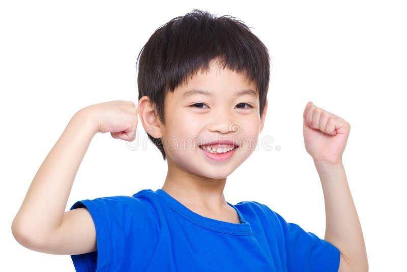 Rapaz pequeno que mostra os músculos do bíceps da mão foto de stock