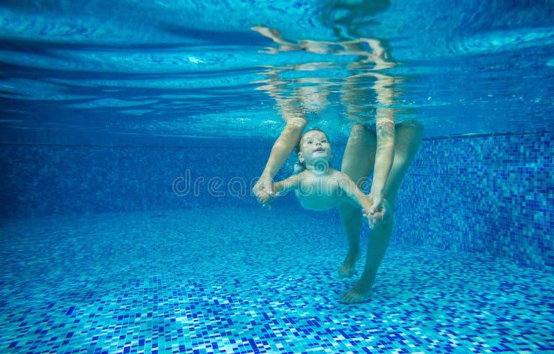 Rapaz pequeno que nadam debaixo d'água, mãe ou instrutor que guardam o imagens de stock royalty free